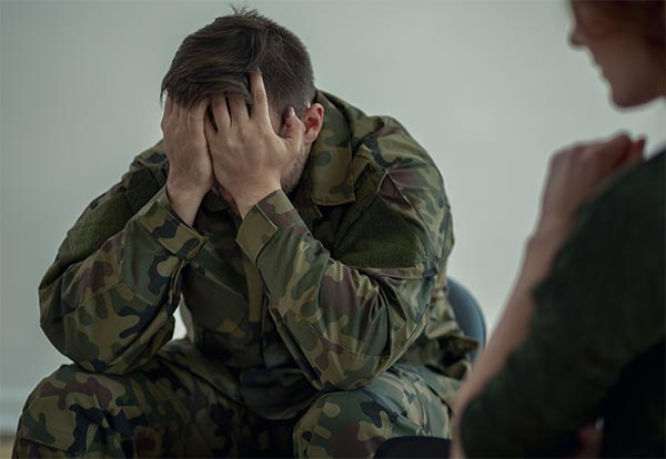 Tired soldier with emotional problems during meeting with psychotherapist