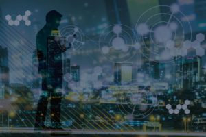 Digital revolution and Internet of Things concept in night city light and silhouette of business man standing and using smart phone with futuristic connection icons.